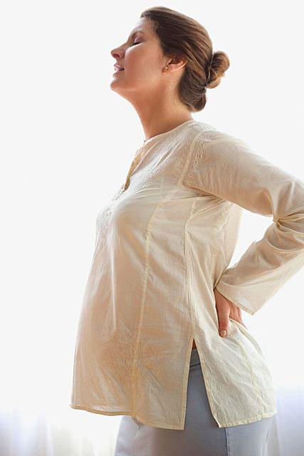 В начале беременности может «стрелять» в пояснице или ломить спину